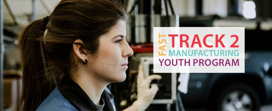 Young Woman Mechanic Looking at the Fast Track To Manufacturing Program Sign